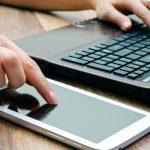 Le mani di una donna lavorano su un computer e un cellulare