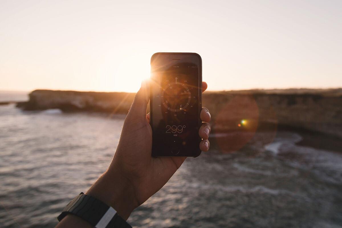 Un cellulare in mano che fotografa un tramonto sul mare