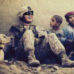 Un soldato seduto in terra circondato da tre bambini e un cane