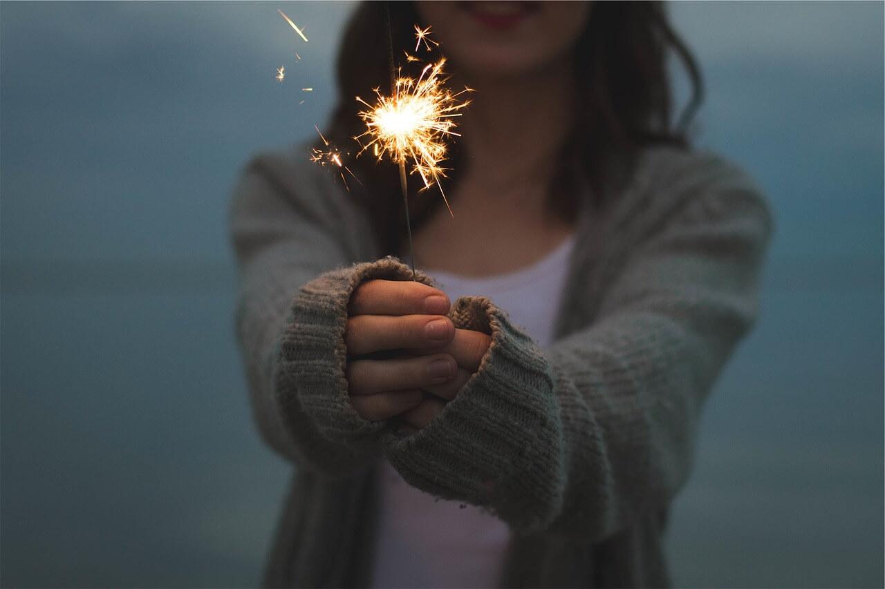 Una ragazza tiene tra le mani una stella filante