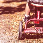 Bambino sul triciclo in un parco